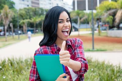 student smiling bringing her folders